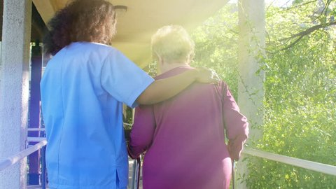 Old woman with crutches helped by nurse outdoor.