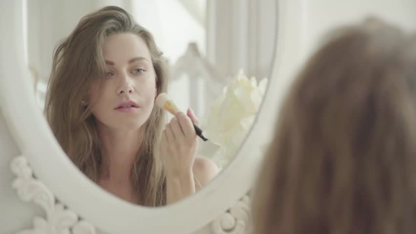 Young woman applies makeup in front of a mirror
