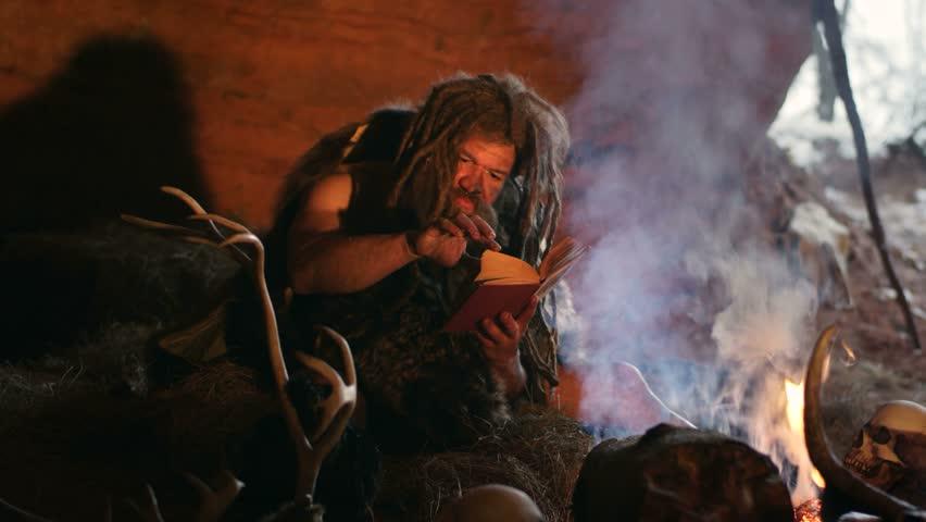 Prehistoric caveman reads book