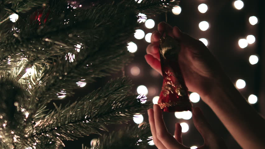 Hanging Christmas decoration on tree with Christmas lights.  Decorating on Christmas tree with ball.