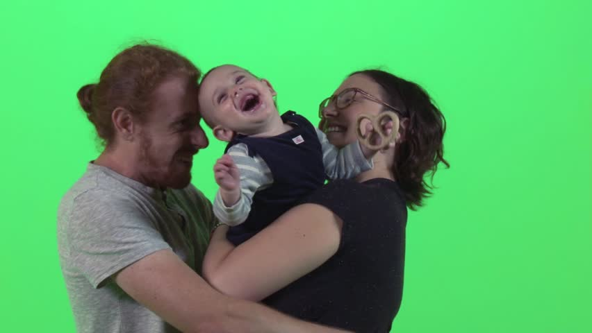 A small baby laughs while mother and father hugging him over a green screen