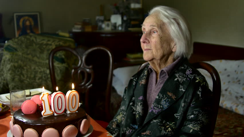 A Hundred Years Old Woman On Her Birthday, Blowing The Candles On Her Cake