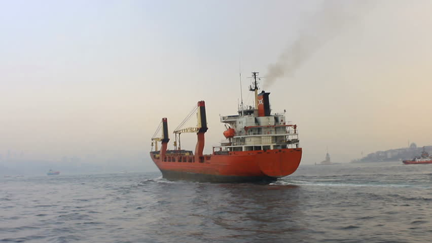 Cargo ship sailing in mist. Tracking shot of the industrial ship. Back view of the red cargo container ship. Istanbul in smog with a cargo ship pass through slowly
