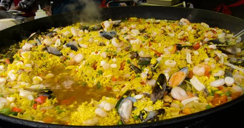 Large pot of paella cooking at a food market