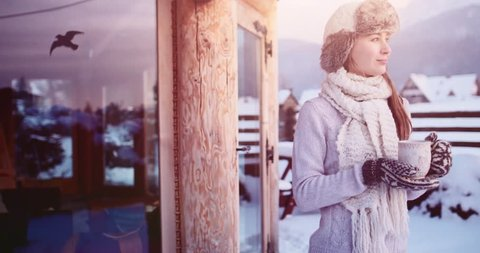 Woman with Cup of Hot Tea or Coffee by the Cozy Mountain Cottage on Snowy Winter. 4K SLOW MOTION 120fps. Beautiful Girl Enjoying Winter Outdoors, drinking from a Mug, getting warm. Christmas Holidays