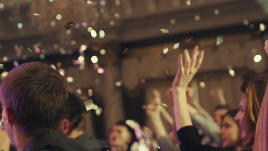 People applausing to the performing musical band in golden confetti and bright stage lights. Inside shooting. A crowd is having fun. Concert atmosphere.