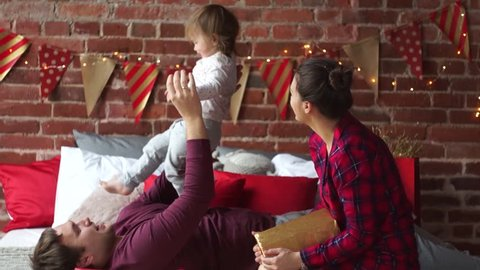 Christmas morning. Young family gleefully congratulates each other Marry Christmas. Young man cheerfully plays with small daughter. Room is festively decorated. Merry Christmas and a Happy New Year.