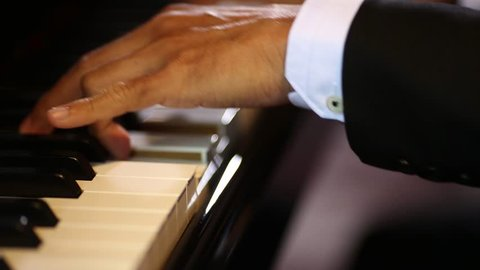 Close up of hands playing on piano