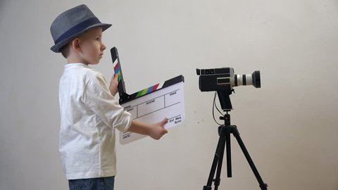 Little child with a clapboard close video camera, action