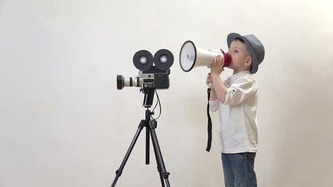 Funny child speaking to megaphone close video camera