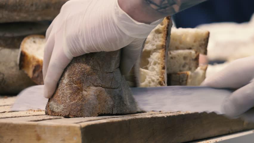 Baker cuts bread on a cutting board, close-up, blurred background #21076024