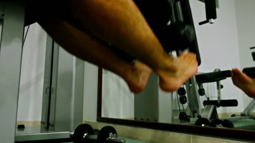 Man Workout In A Gym Closeup Of Male Feet Pulling Weight Machine
