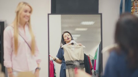 Two young women walking through the mall. Woman shopping. Young woman chooses a dress in a clothing store and consults with friend. Trying on dresses in the mirror.