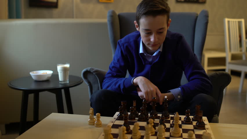 Teenager boy plays chess