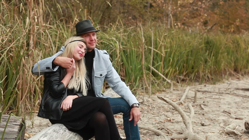Couple in love sitting on big log in reeds and… - Royalty