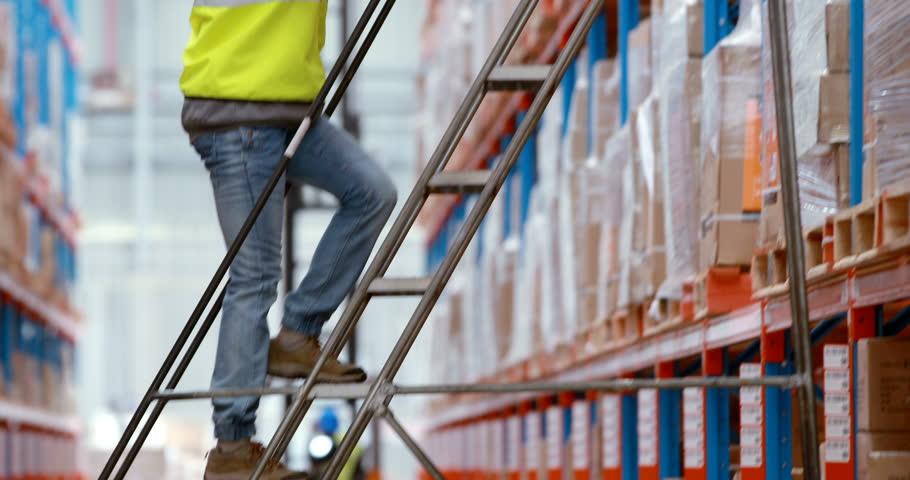 Male warehouse worker using ladder to arrange cardboard box in the warehouse 4k | Shutterstock HD Video #21123751