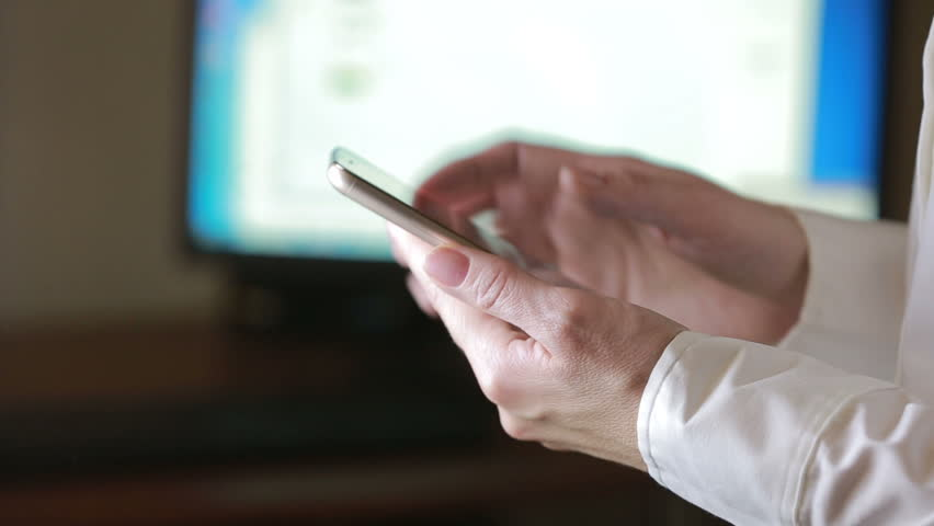 Close up of a woman using mobile smart phone. the background monitor | Shutterstock HD Video #21138691