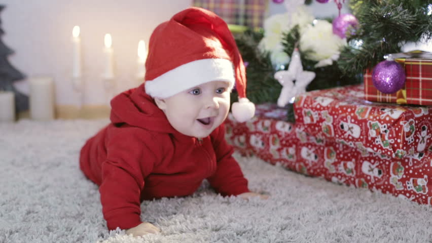 6a7ea366ef6b8 Funny small child in a red santa suit playing with a toys on the Christmas  tree