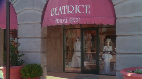 day Tight entrance Raked right Beatrice Bridal Shop wedding gowns mannequins display window Upscale couple thru