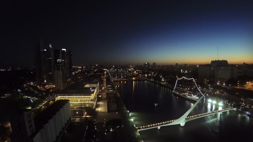AERIAL: Puerto Madero harbor, Buenos Aires, at night, with restaurant buildings, a promenade, a museum ship and high-rise buildings of the city center