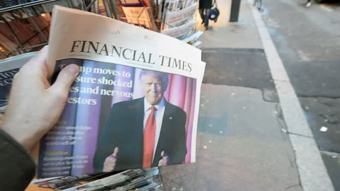 PARIS, FRANCE - NOV 10, 2016: Man buying Financial Times newspaper with shocking title at press kiosk about the US President Elections - Donald Trump is the 45th President of United States of America