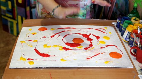 Abstract acrylic intuitive painting process. Woman artist drawing picture with hands and tools