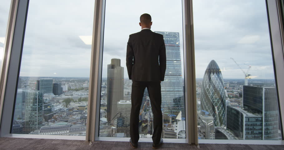 4K View from behind of young successful business executive looking out at view of the city. View from the window shows famous London skyline with iconic buildings. Slow motion.