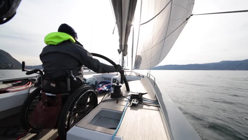 The invalid man in the wheel chair driving a sail boat