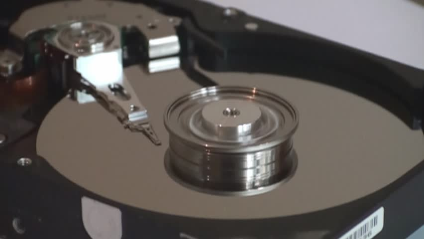Metal circle plate and magnetic head inside hard disk drive reading and writing data | Shutterstock HD Video #21255601
