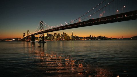Aerial sunset low angled water view under the illuminated two levels of Oakland Bay Bridge, San Francisco, America