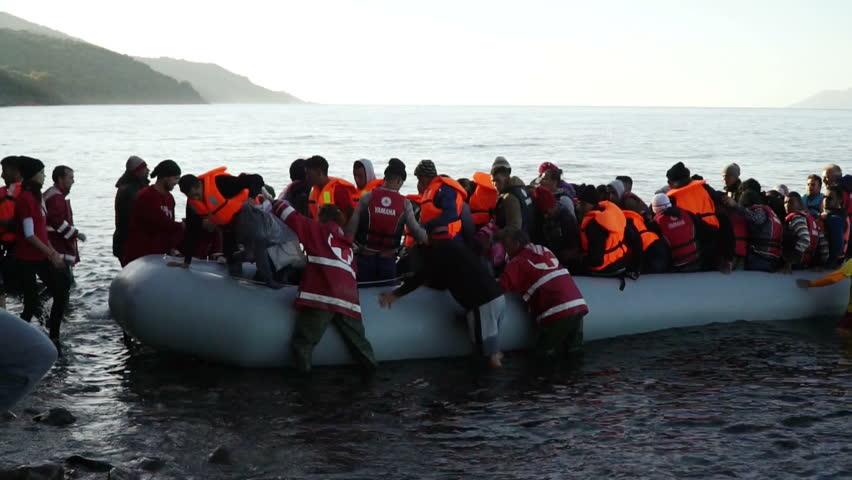 LESVOS, GREECE - NOV 5, 2015: Refugees leave rubber dinghy near the shore.
