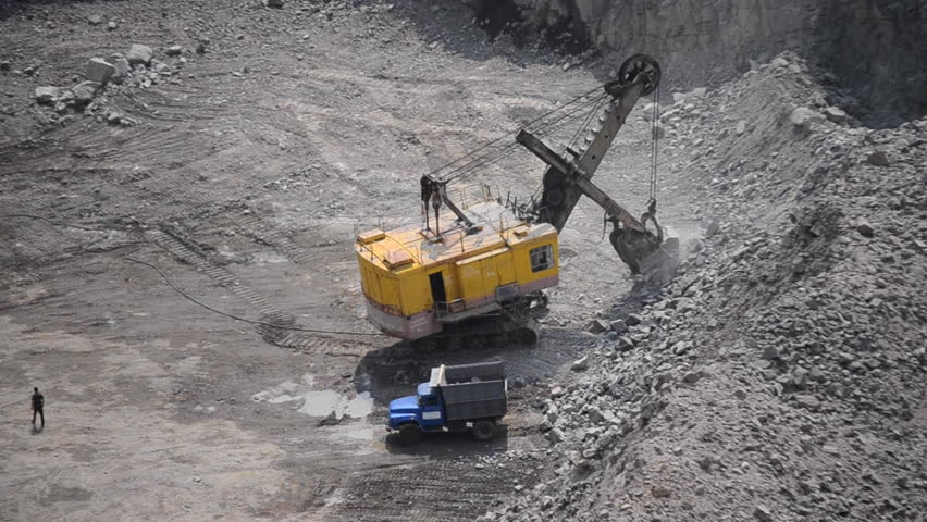 big huge yellow excavator bucket scoops up large stones granite and pours close, huge excavator and truck and man granite quarry and man standing next to waiting different sizes, top view, with sound