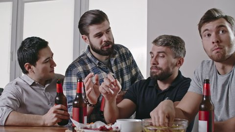 Male friends sitting at home on Friday drinking beer, chatting and watching football match