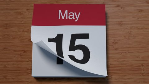 Calendar for May on wooden table flipping through days of month