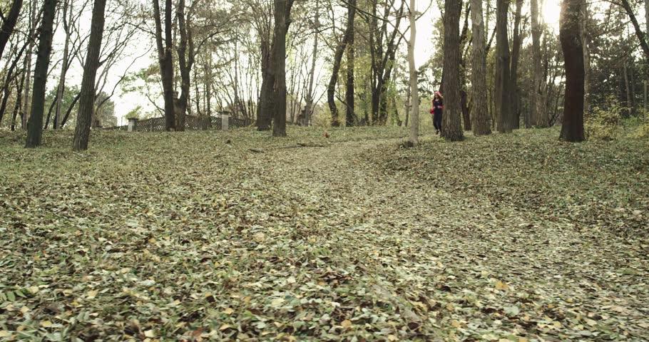 Fitness girl runs through the park in the morning. Slowmotion. 4k DJI Ronin shot.