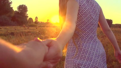 Follow me. Happy couple taking hands and having fun outdoors. Couple running away on the meadow. Countryside. Young Man and woman running through a field, Sun flare. Slow motion 240fps HD 1080