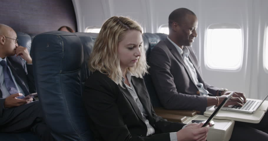 Young Caucasian woman reads a tablet computer while African American man  types on a laptop beside her in business class / first class section of passenger airliner.  Medium shot with camera dolly
