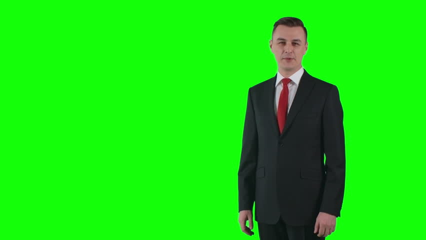 Man in business suit standing against green screen backdrop showing something and talking | Shutterstock HD Video #21385141