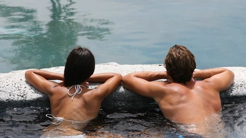 Wellness Spa - couple relaxing in hot tub whirlpool jacuzzi outdoor at luxury resort spa retreat. Happy young woman and man relaxed resting in water near pool on travel vacation holidays. 59.94 FPS.