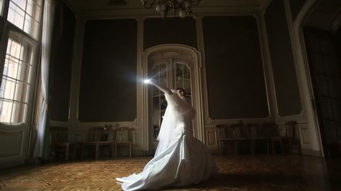 Pretty amusing bride with lightsaber in the dark room.