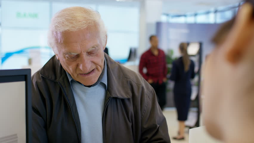 4K Worker at customer service desk assisting queue of customers in modern bank. Shot on RED Epic.