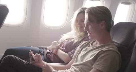 Attractive young couple enjoy watching online content on a smart phone as they fly in main cabin of commercial jet airliner. Medium shot from side angle, recorded hand-held at 60fps