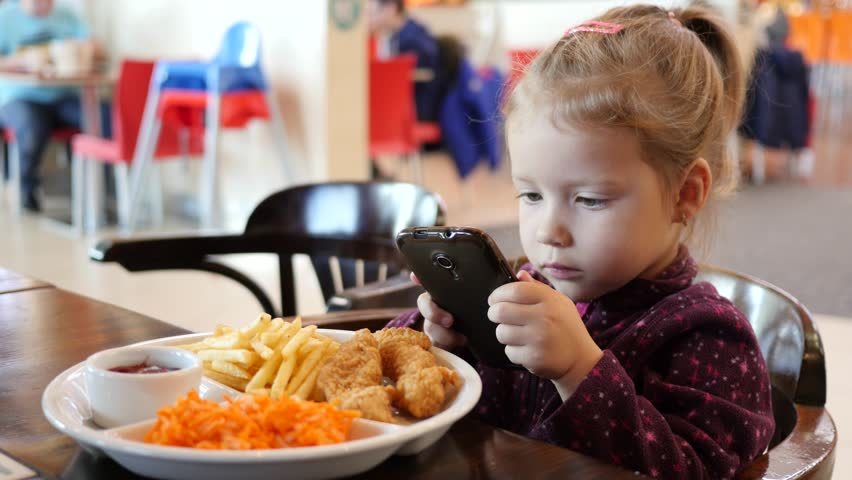 Little kid girl make dish photo via smart phone during eating in fast food court in a mall