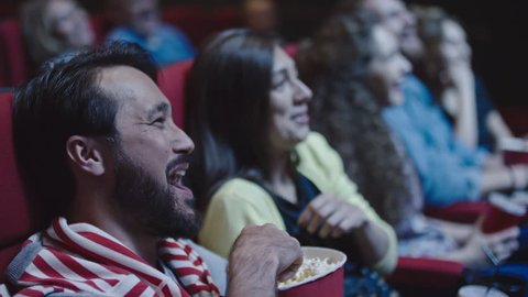 Closeup of young couple sharing popcorn while watching comedy in movie theater