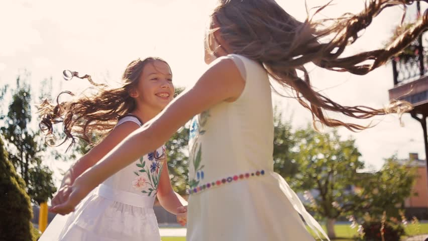 Cute children in a white dresses whirl in round dance on grass in a bright sunlight. Two little girls with curly haircuts whirling in round dance. Moments of happiness. Childhood happiness, laughing.