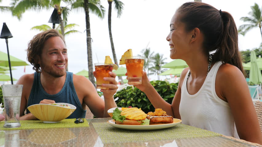 Couple dating having fun drinking alcohol at beach club with alcoholic drink beverage Mai Tai cocktail on Hawaii. Portrait of romantic young mixed race couple on honeymoon romance on Hawaiian beach.