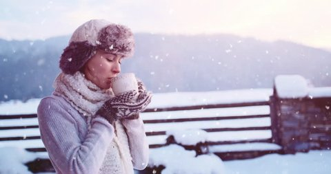 Woman drinking Hot Tea or Coffee from Festive Cup with Snowy Mountain View on Background. 4K SLOW MOTION 120fps. Beautiful Girl Enjoying Winter Morning or Evening Outdoors. Christmas Holidays