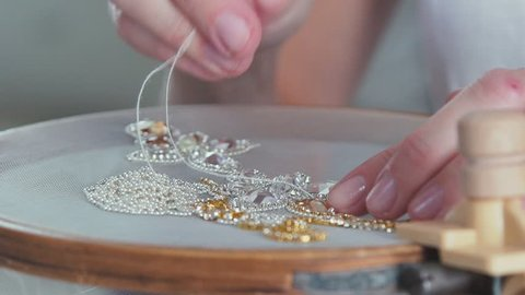 Slow motion. Close-up of mosaic stones diamond embroidery. The needle comes out of the canvas. Embroidery artificial shiny stones. Creating jewelry handmade jewelry. Decorative embroidery.