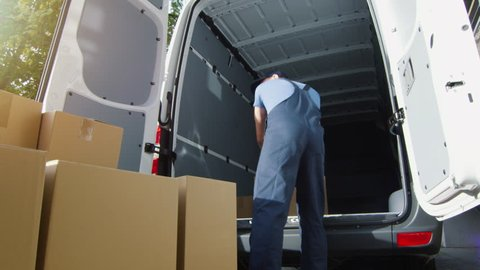 Delivery Man Loads Cardboard Boxes into his Van. Slow Motion. Shot on RED Cinema Camera in 4K (UHD).