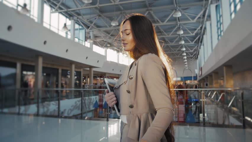 Young female passenger at the airport, with her tablet computer while waiting for her flight walking in terminal. Elegant businesswoman in office with laggage, shopping mall
